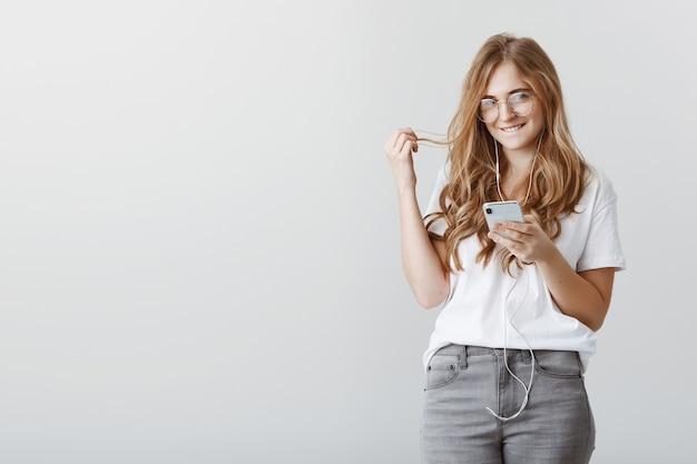 Mit bösen ideen im sinn. porträt des schönen charmanten blonden studenten in der brille, das smartphone hält, auf die lippe beißt und mit den haaren spielt, neugierig lächelt, flirtet oder in romantischer stimmung ist