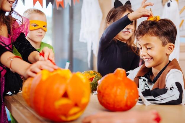 Mit bruder spielen. nette jüngere schwester, die katzenkostüm für halloween trägt, das mit niedlichem hübschem bruder spielt