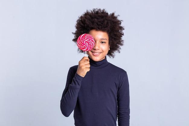 Mit bunten süßigkeiten. strahlender lockiger junger mann, der sein gesicht mit süßen roten süßigkeiten schließt, während er für kameramänner posiert