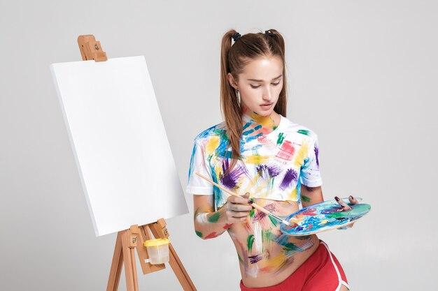 Mit bunter farbe verschmutzte malerin zeichnet auf leinwand