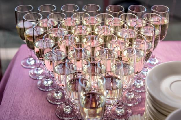 Mit champagner gefüllte gläser, nahaufnahme. reihen von gläsern weißwein beim festlichen abendessen. willkommensgetränk.