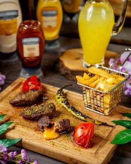 Mit cheddar-käse gefüllter lammkebab, serviert mit pommes frites, gegrillter tomate und pfeffer