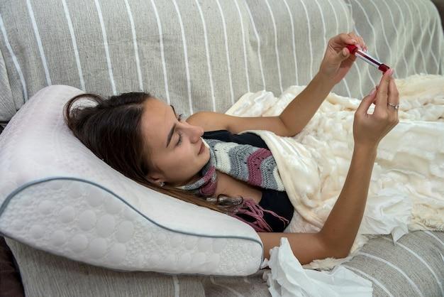 Mit covid-19-grippe infizierte frau liegt im bett und schaut ihr positives reagenzglas auf das corona-virus an