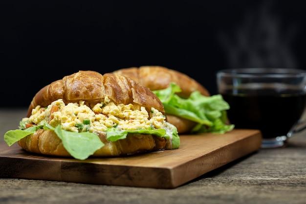 Mit croissant gefüllte rühreier auf holztablett mit heißem kaffeehintergrund.