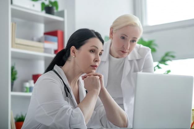 Mit dem patienten sprechen. zwei ärztinnen, die eine videokonferenz mit der patientin haben und ernst aussehen