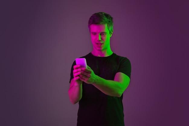Mit dem smartphone selfie, vlog. porträt des kaukasischen mannes auf purpurrotem studiohintergrund im neonlicht. schönes männliches modell im schwarzen hemd. konzept der menschlichen emotionen, gesichtsausdruck, verkauf, anzeige.