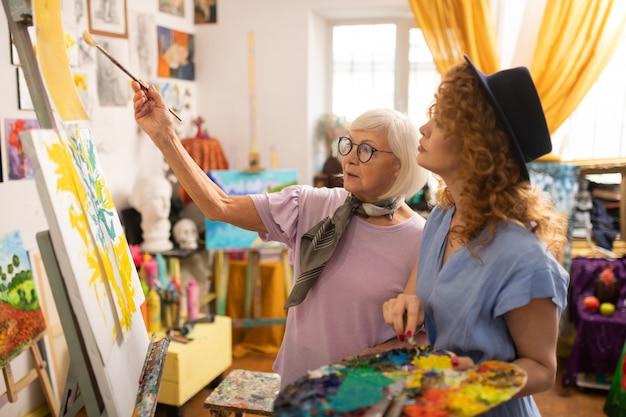 Mit dem studenten sprechen. alter grauhaariger kunstlehrer in brille, der mit ihrer schülerin spricht und einige fehler zeigt