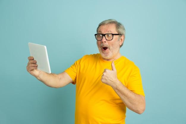 Mit dem tablet den daumen nach oben zeigen. kaukasisches mannporträt lokalisiert auf blauem studiohintergrund. schönes männliches modell im gelben hemd.