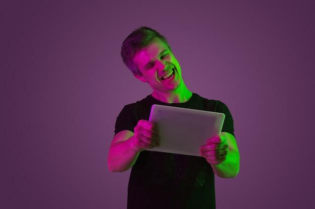 Mit dem tablet spielen, genießen. porträt des kaukasischen mannes auf purpurrotem studiohintergrund im neonlicht. schönes männliches modell im schwarzen hemd. konzept der menschlichen emotionen, gesichtsausdruck, verkauf, anzeige.