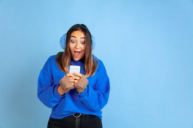 Mit dem telefon glücklich. porträt der kaukasischen frau auf blauem raum. schönes weibliches modell in warmer kleidung