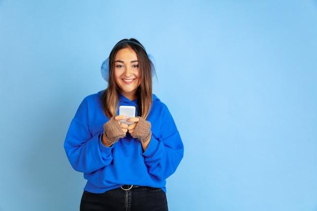 Mit dem telefon glücklich. porträt der kaukasischen frau auf blauem studiohintergrund. schönes weibliches modell in warmer kleidung. konzept der menschlichen emotionen, gesichtsausdruck, verkauf, anzeige. winterstimmung, ferien.