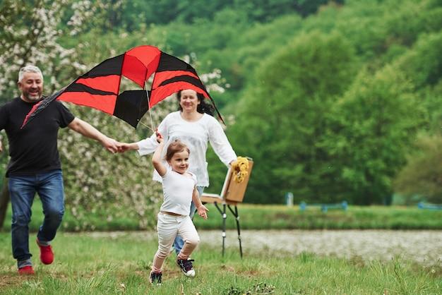 Mit den händen halten. positives weibliches kind mit großmutter und großvater, die mit rotem und schwarzem drachen in den händen draußen laufen