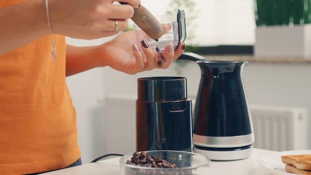 Mit der kaffeemühle frischen kaffee zum frühstück zubereiten. hausfrau zu hause, die frisch gemahlenen kaffee in der küche zum frühstück zubereiten, trinken, kaffee-espresso mahlen, bevor sie zur arbeit geht