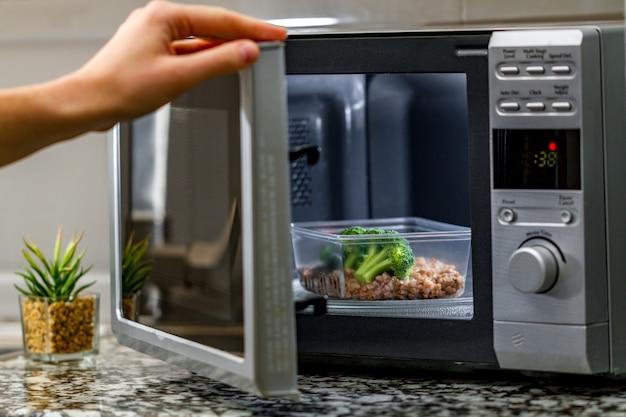 Mit der mikrowelle speisen erhitzen. kunststoffbehälter mit brokkoli und buchweizen in der mikrowelle erhitzen