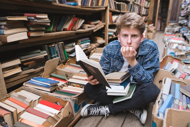Mit einem buch in den händen auf dem boden in einer öffentlichen bibliothek sitzen und mit erstauntem blick in die kamera schauen