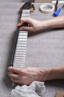 Mit einem lineal prüft der meister, ob der gitarrenhals deformiert ist.