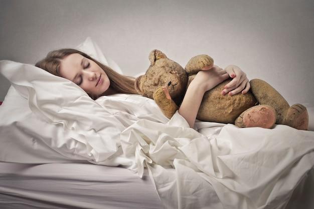 Mit einem teddybären schlafen