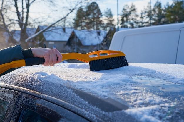 Mit einer bürste schnee vom dach eines autos räumen