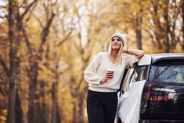 Mit einer tasse getränk in den händen. mädchen haben eine herbstreise mit dem auto. modernes brandneues auto im wald.