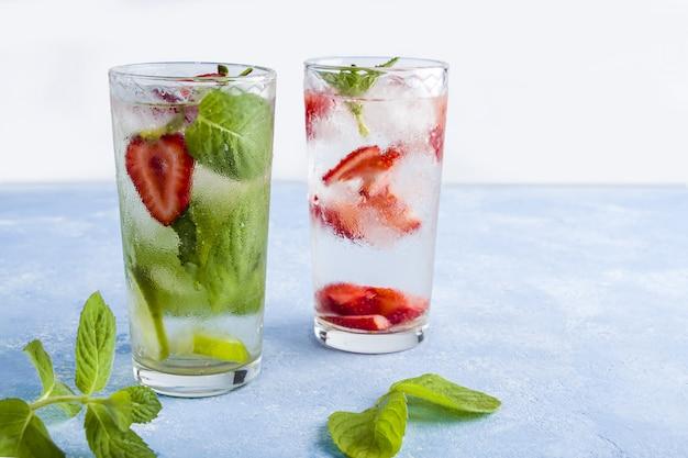 Mit erdbeere, limette, kirsche und minze trinken. sommerlimonaden oder eistee. mojito-cocktails mit eiswürfeln.