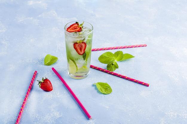 Mit erdbeere, limette und minze trinken. sommerlimonaden oder eistee. mojito-cocktails mit eiswürfeln.