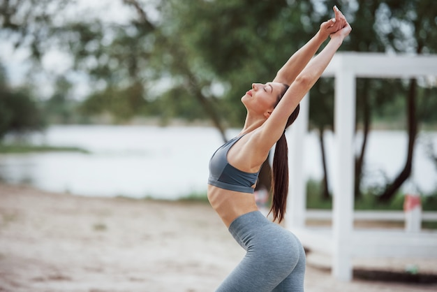 Mit erhobenen händen. brünette mit schöner körperform in sportlicher kleidung haben fitness-tag am strand