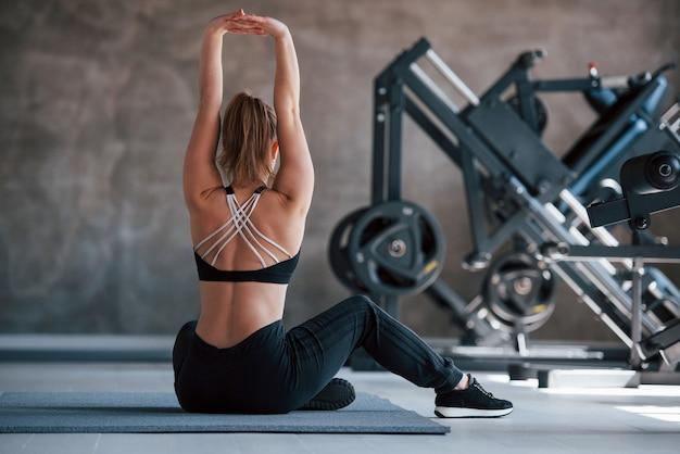 Mit erhobenen händen. foto der herrlichen blonden frau im fitnessstudio zu ihrer wochenendzeit