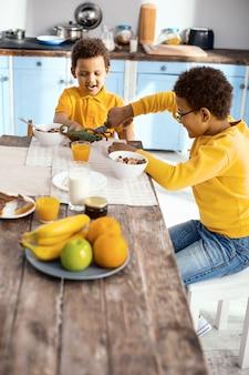 Mit fantasie. angenehme kleine jungen, die am küchentisch sitzen und mit ihren spielzeugdinosauriern kämpfen