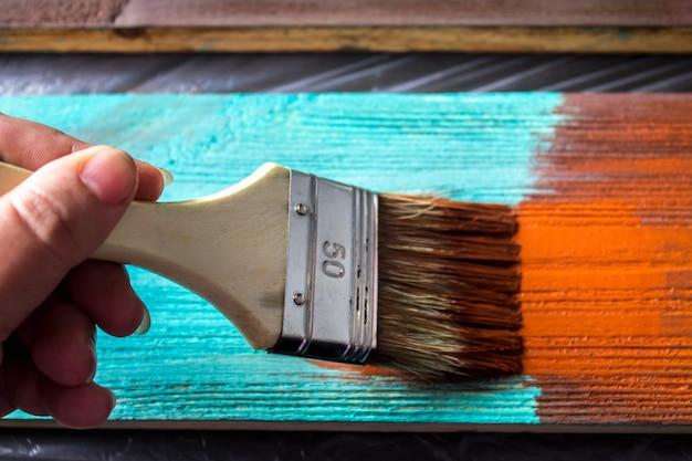 Mit farbe in die hand streichen. ein mann malt blaue bretter in einem braunen pinsel.