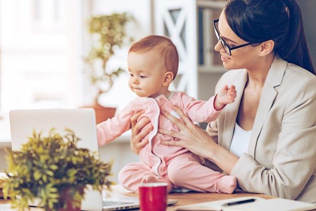 Mit freude zusammenarbeiten. fröhliche junge schöne geschäftsfrau, die ihr baby mit einem lächeln betrachtet, während sie an ihrem arbeitsplatz sitzt