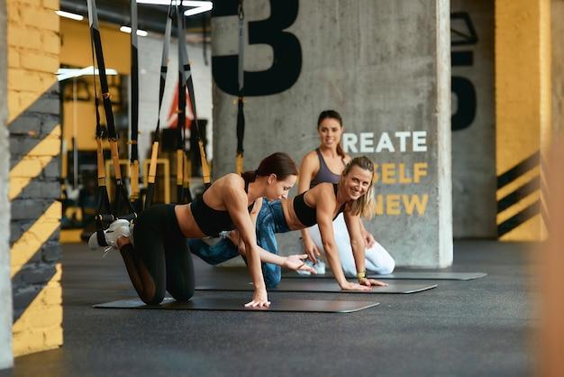 Mit freunden trainieren. drei junge positive frauen sprechen und diskutieren etwas, während sie mit trx-fitnessgurten im fitnessstudio trainieren. sport, workout, wellness und gesunder lebensstil