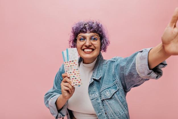 Mit freundlichen grüßen helle frau mit stilvollen lila frisur in jeansjacke hält tickets, lächelt und nimmt selfie.