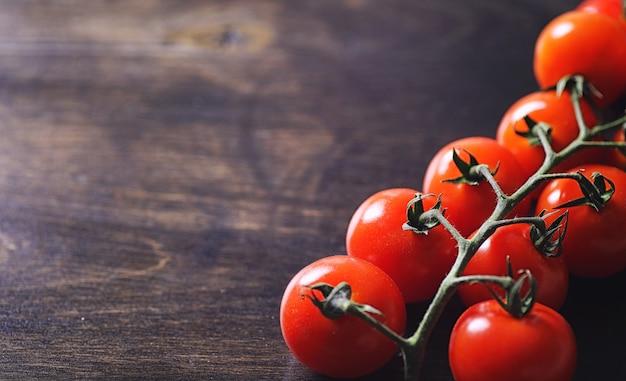 Mit frischen kirschtomaten verzweigen. reife rote tomaten