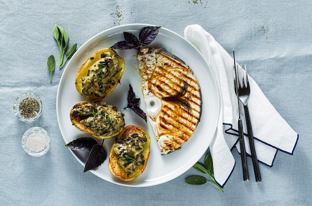 Mit gebackenen pilzkartoffeln und schwertfischsteak servieren. gesundes mittag- oder abendessen für die familie