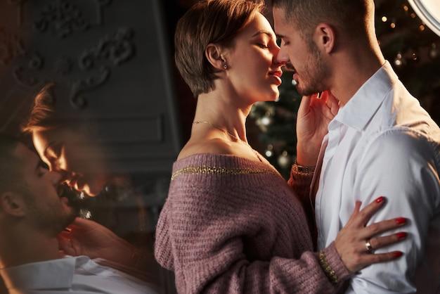 Mit gefühl. die nähe des mannes und des mädchens in luxuskleidung, die tanzen und flirten. wunderschöne spiegelung von der seite.