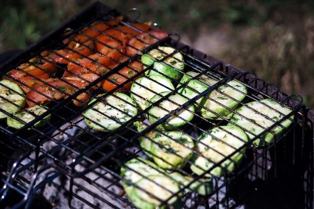 Mit geröstetem gemüse grillen: zucchini und tomaten. abendessen im sommer.