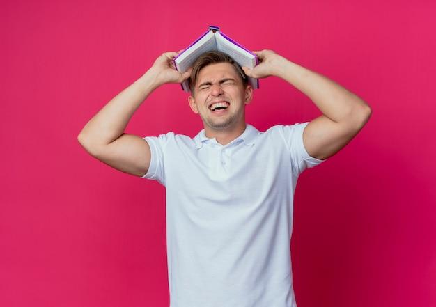 Mit geschlossenen augen bedeckte freudiger junger hübscher männlicher student kopf mit buch lokalisiert auf rosa wand