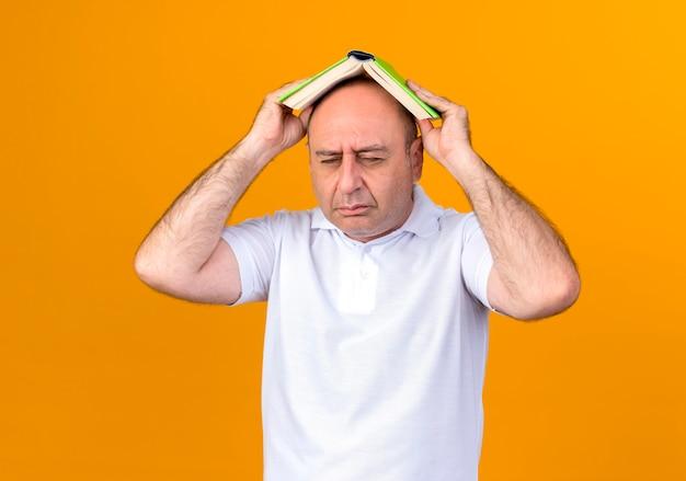 Mit geschlossenen augen bedeckte trauriger lässiger reifer mann bedeckten kopf mit buch, das auf gelber wand lokalisiert wird