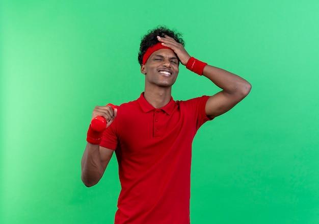 Mit geschlossenen augen beeindruckt junger sportlicher mann mit stirnband