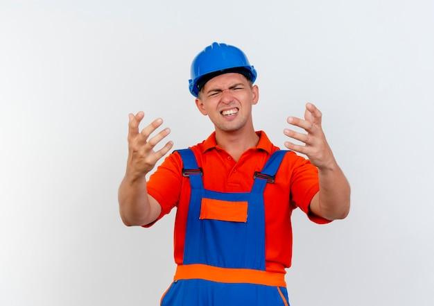 Mit geschlossenen augen besorgt junger männlicher baumeister, der uniform und schutzhelm trägt, hält hände zur kamera auf weiß