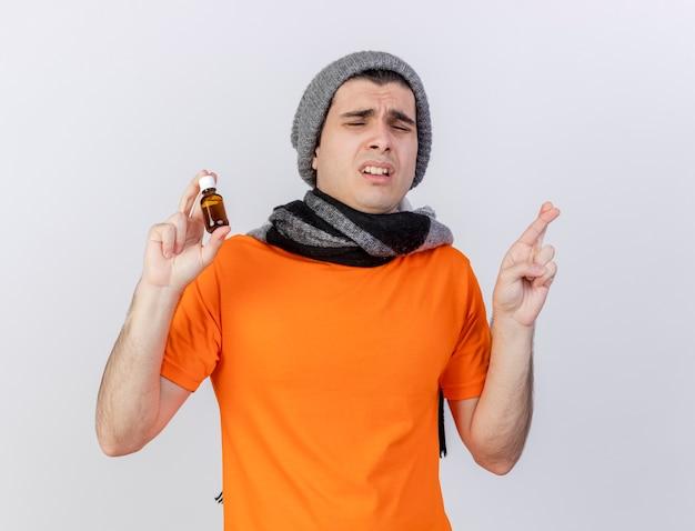 Mit geschlossenen augen besorgter junger kranker mann, der wintermütze mit schal hält medizin in glas hält