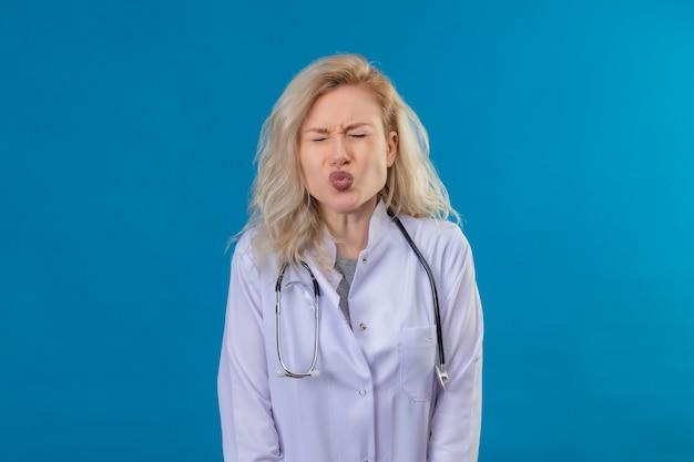 Mit geschlossenen augen doktor junges mädchen, das stethoskop im medizinischen kleid trägt, das kussgeste auf blauem hintergrund zeigt