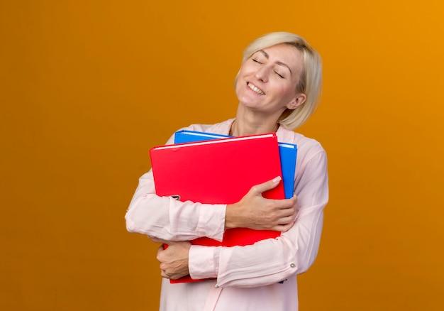 Mit geschlossenen augen erfreut junge blonde slawische frau, die ordner lokalisiert auf orange wand hält