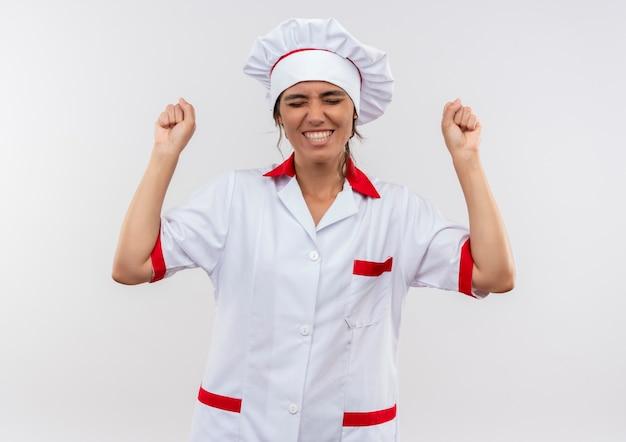 Mit geschlossenen augen freudige junge köchin in kochuniform zeigt ja geste mit kopierraum