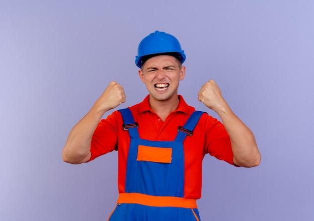 Mit geschlossenen augen freudiger junger männlicher baumeister, der uniform und schutzhelm trägt, zeigt ja geste auf lila