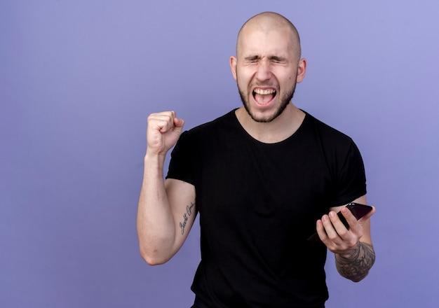 Mit geschlossenen augen freudiger junger sportlicher mann, der telefon hält und ja geste zeigt, die auf lila isoliert wird