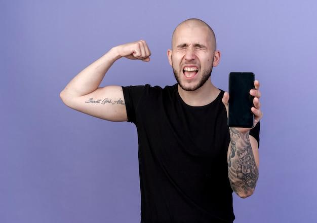 Mit geschlossenen augen freudiger junger sportlicher mann, der telefon hält und starke geste zeigt, die auf purpur isoliert wird