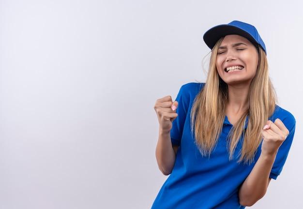 Mit geschlossenen augen freudiges junges liefermädchen, das blaue uniform und kappe trägt, die ja geste lokalisiert auf weiß zeigt