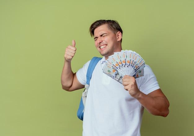 Mit geschlossenen augen glücklicher junger hübscher männlicher student, der rückentasche hält, die bargeld und seinen daumen oben auf olivgrün hält