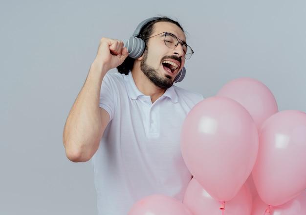 Mit geschlossenen augen hören freudiger gutaussehender mann, der eine brille hält, die luftballons hält, musik auf kopfhörern, die auf weiß isoliert werden